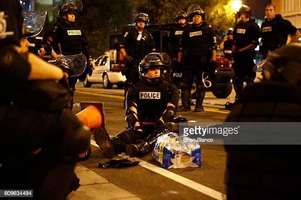 Police officers take a moment to rest after a night of clashing with rioters protesting the death of Keith Scott September 22 2016 in Charlotte North...