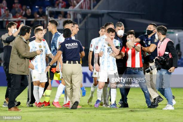 Police officers take action as pitch invaders try to get close to Lionel Messi of Argentina after a match between Paraguay and Argentina as part of...
