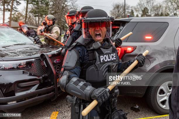 Police officers take cover as they clash with protesters after an officer shot and killed a black man in Brooklyn Center, Minneapolis, Minnesota on...