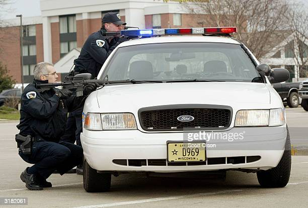 Police officers take cover behind a squad car near where University of Wisconsin student Audrey Seiler was found March 31 2004 in Madison Wisconsin...