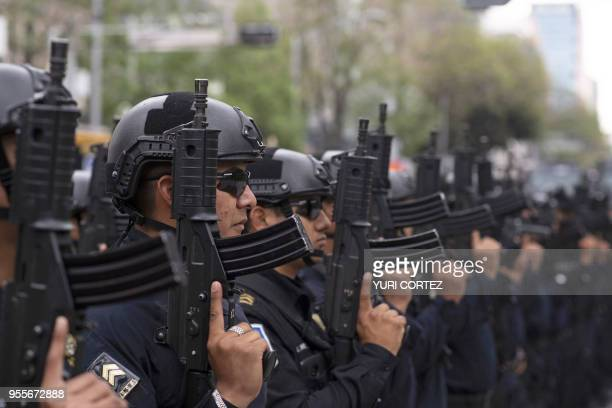 Police officers take part in a parade in tribute to three slain fellow policemen near Benito Juarez's monument in Mexico City on May 7 2018 According...