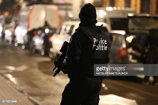 Police officers take part in an operation in Schaerbeek Schaarbeek Brussels late on March 24 2016 Six people were arrested on March 24 2016 in a...