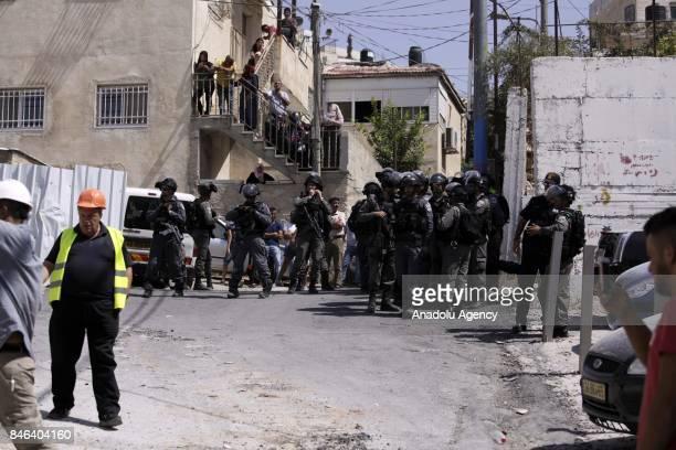 Police officers take security measures as a bulldozer demolishes a twostorey building belongs to Palestinian siblings Muttasim and Muntasir Ebu Farha...