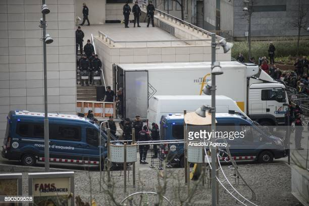 Police officers take security measures at the entrance of the Lleida museum as workers carry 44 pieces of religious art to the trucks after the...