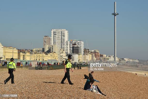 Police officers talk to people on a near-deserted beach in Brighton, on the south coast of England, on April 5 as the warm weather tests the...