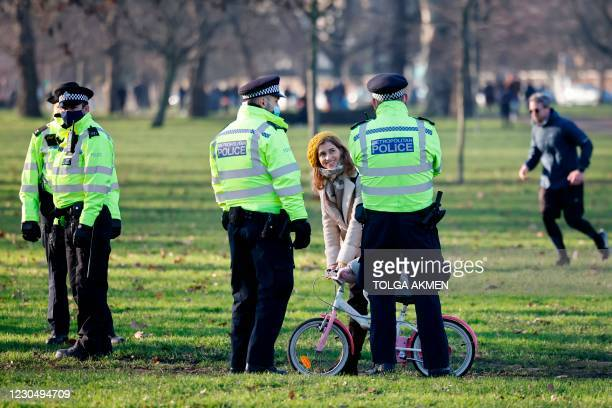 Police officers talk with a family as they patrol in Clapham Common, south London, on January 9, 2021 as life continues in Britain's third lockdown...