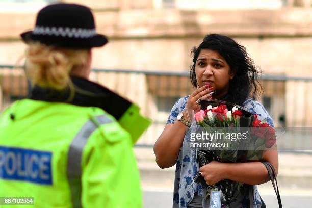 A police officers talk with a woman carrying a bunch of flowers near the Manchester Arena in Manchester northwest England on May 23 2017 following a...