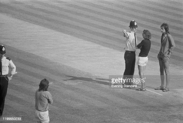 Police officers talking to pitch invaders during the 5th Test between England and the West Indies at the Oval in London, England, August 1976.