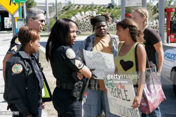 Police officers talking to protestors at the groundbreaking ceremony for affordable housing at Pinnacle Park