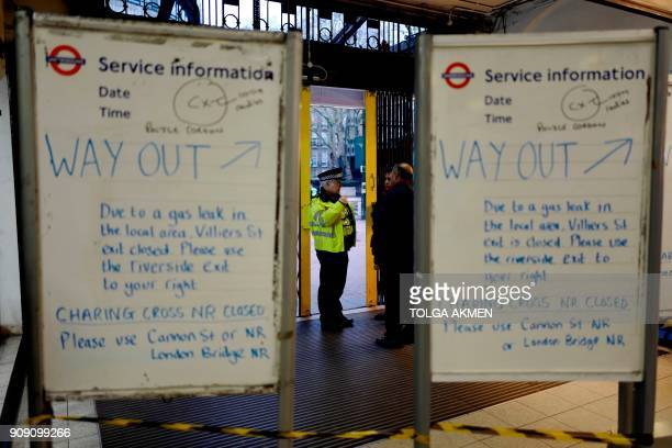 A police officers talks with passaengers beyond notice boards at Embankment tube station advising passengers of a gas leak closing the Strand and...