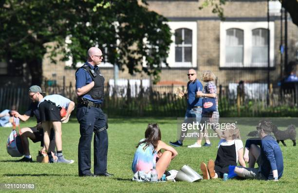 Police officers tell members of the public that they are not allowed to sit and enjoy the sunshine on the grass, but are allowed to walk to take...