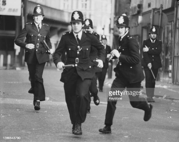 Police officers, truncheons in hand, seen during a charge as violence erupts on the streets of Brixton, London, England, 13th April 1981.