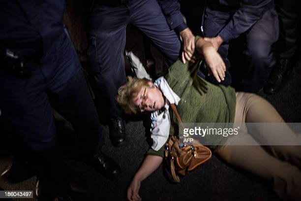 Police officers try to help a woman who has passed out during clashes at a rally against the Rosia Montana Gold Corporation a Canadian gold mine...