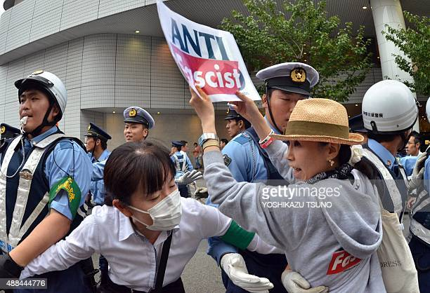 Police officers try to hold back demonstrators attempting to stop a vehicle transporting members of the parliament's Upper House security bills...