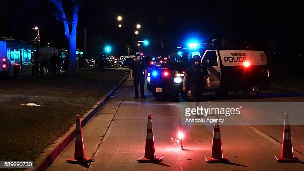 Police officers try to keep away protesters from the area as they construct barricade near the damaged gas station during a protest held for Sylville...