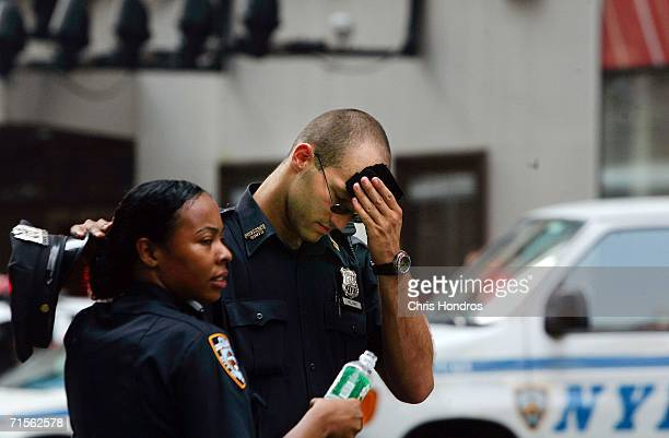 Police officers try to keep cool in Times Square while onduty during a visit by US Treasury Secretary Henry Paulson to the Nasdaq stock market August...