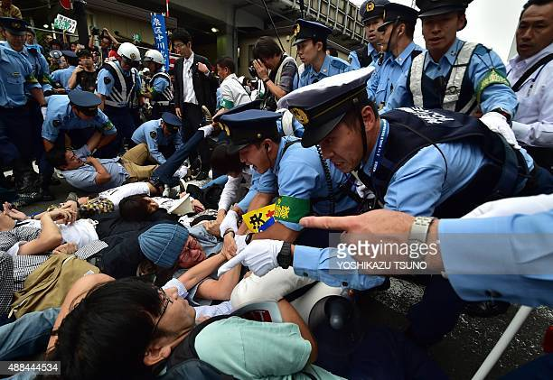 Police officers try to remove demonstrators lying on the ground to stop a vehicle transporting members of the parliament's Upper House security bills...