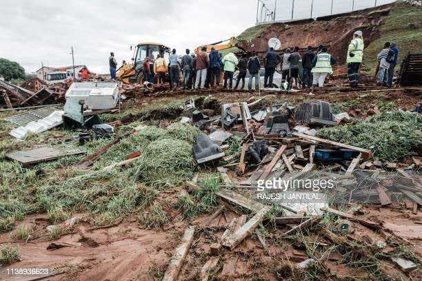 Police officers try to rescue people trapped in their homes destroyed in a mudslide following torrential downpours and flash floods near Westcliff...
