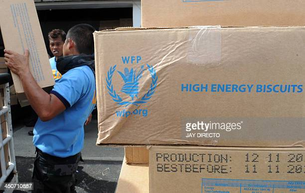 Police officers unload WFP High Energy Biscuits from a military plane at Roxas City airport on November 20 2013 Some 600000 survivors of a deadly...