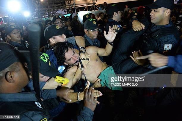 Police officers use a Taser gun on a demonstrator during a protest against corruption and the governor of the state of Rio de Janeiro Sergio Cabral...