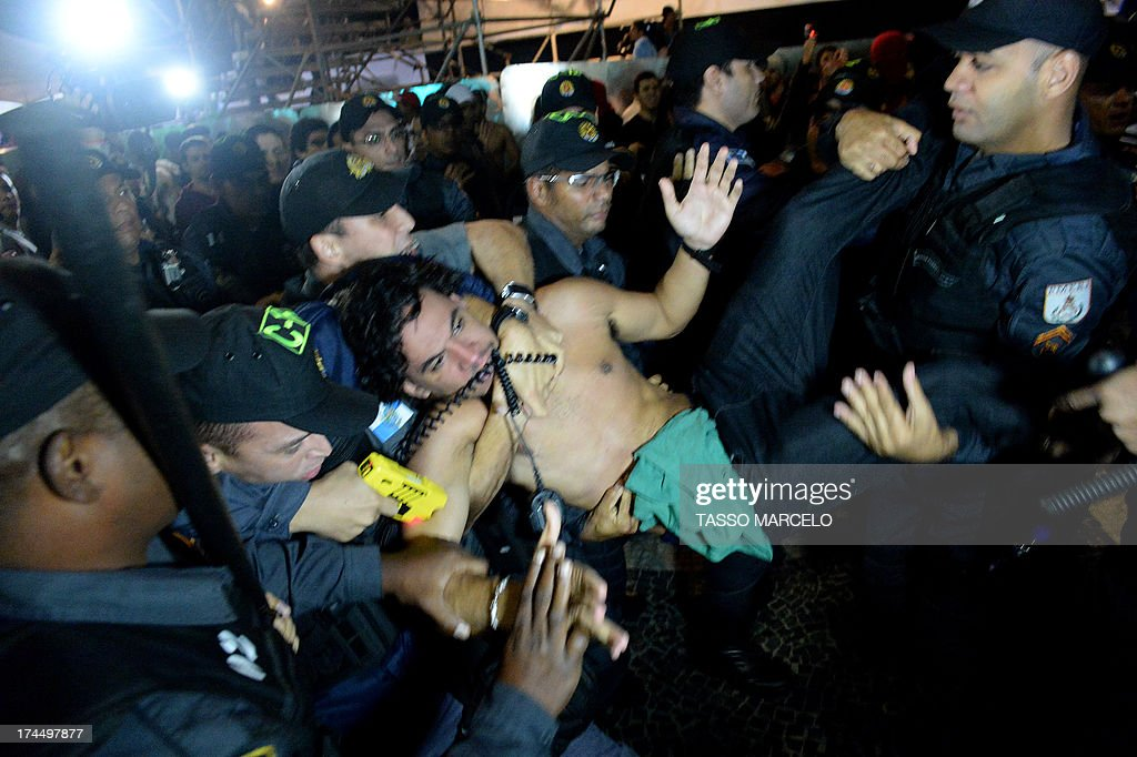 Police officers use a Taser gun on a demonstrator during a protest against corruption and the governor of the state of Rio de Janeiro, Sergio Cabral, which got near the stage where visiting Pope Francis was wrapping up a massive ceremony with hundreds of thousands of young Catholics at Copacabana beach in Rio de Janeiro, on July 26, 2013. Pope Francis, who is in Rio for the weeklong gathering of young Catholics World Youth Day, took his high-octane mission to 'shake up' Catholic faith back to the streets of Brazil Friday, greeting throngs of pilgrims, meeting convicts and hearing youngsters confess their sins.