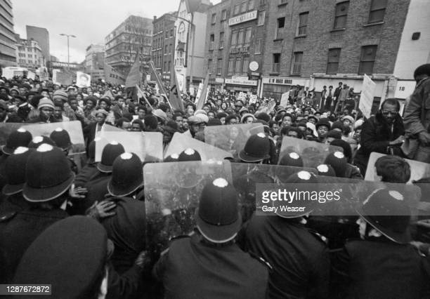 Police officers use a wall of riot shields to hold back demonstrators marching from New Cross to the House of Commons in what the organisers - New...