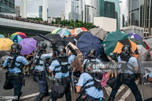 Police officers use baton to disperse antiextradition protesters during a clash outside the Legislative Council Complex ahead of the annual flag...