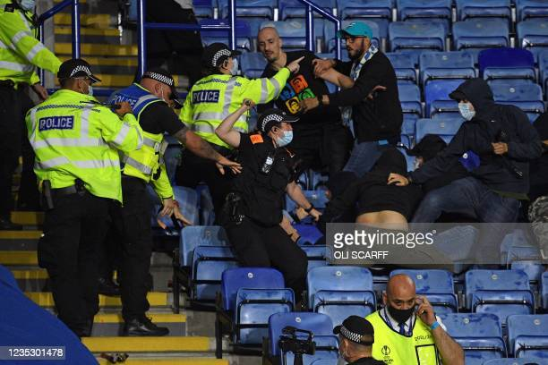 Police officers use batons as they hold back Napoli fans attempting to clash with Leicester fans after the final whistle during the UEFA Europa...