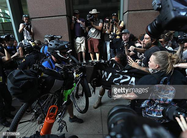 Police officers use bicycles to push back protesters during a demonstration near the site of the Republican National Convention on July 19 2016 in...