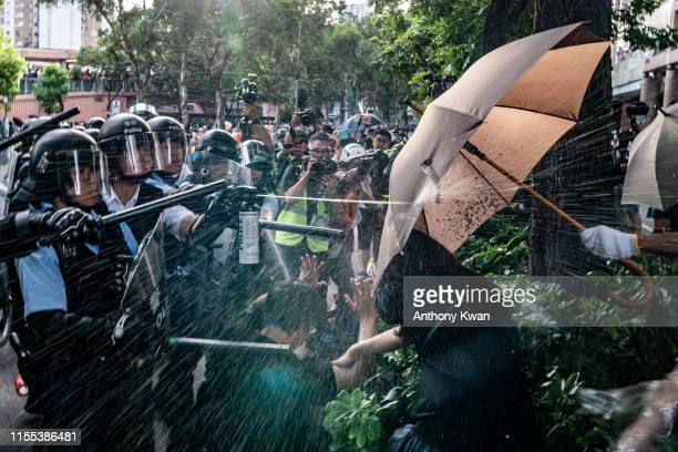 Police officers use pepper spray to disperse protesters after a rally in Sheung Shui district on July 13 2019 in Hong Kong China Protesters in Hong...