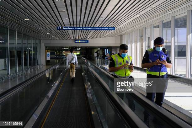 Police officers use smartphones while standing on a travelator at Kuala Lumpur International Airport in Sepang, Selangor, Malaysia. On Friday, June...