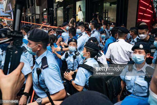 Police officers use tape to cordon off areas on the 24th anniversary of Hong Kong's handover from Britain in the Causeway Bay district on July 1,...