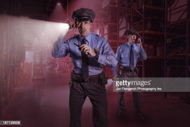 Police officers using walkie talkies in warehouse