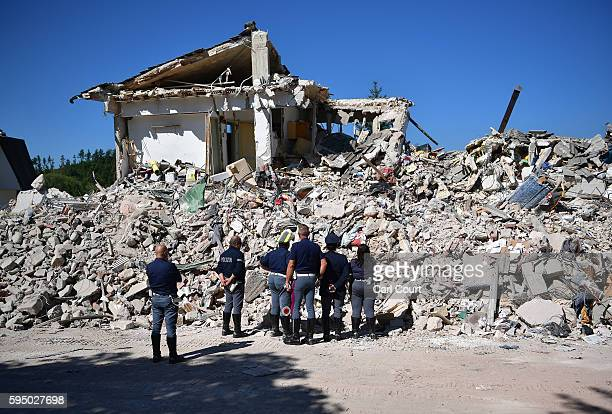 Police officers view the remains of a building that was destroyed during an earthquake on August 25 2016 in Amatrice Italy The death toll in the 62...