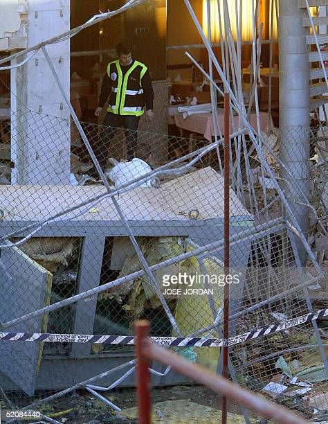 Police officers view the scene at the Mediterranean resort Port Denia Hotel in Denia where a bomb exploded 30 January 2005 injuring two people. The...
