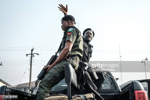Police officers wait to escort staff of the Independent National Electoral Commission with electoral items to a polling station from a Registration...