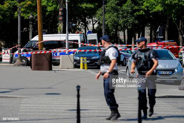 TOPSHOT Police officers walk accross a sealed off area on June 19 2017 on the ChampsElysees avenue in Paris after a car crashed into a police van...