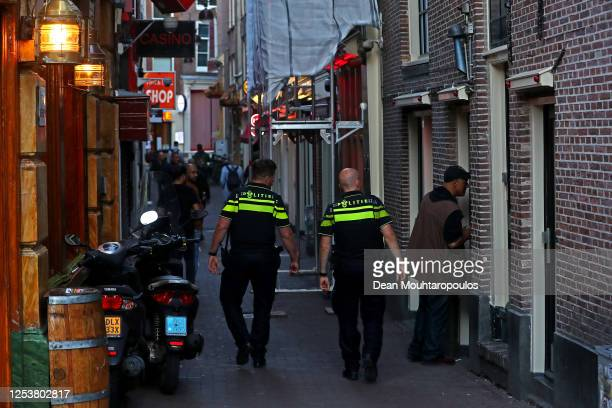 Police officers walk along the Red Light District as it reopens after the Coronavirus or Covid19 Lockdown on July 01 2020 in Amsterdam Netherlands...