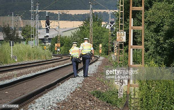 Police officers walk along train tracks in Wuerzburg southern Germany on July 19 2016 a day after a man attacked train passengers with an axe German...