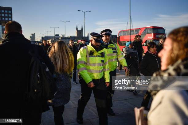 Police officers walk among commuters on London Bridge, after it was reopened following the terror attack, on December 2, 2019 in London, England....