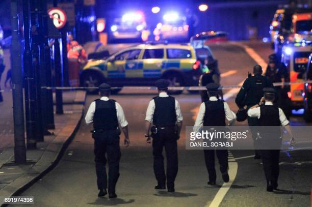 Police officers walk at the scene of an apparent terror attack on London Bridge in central London on June 3 2017 Armed police fired shots after...