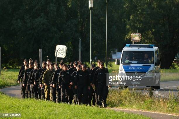 Police officers walk back from the crash site of one of two Bundeswehr Eurofighter fighter jets on June 24, 2019 near Nossentin, Germany. Two...