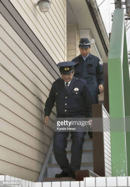 Police officers walk down the stairs of an apartment house in Zama Kanagawa Prefecture on Oct 31 2017 where police found nine bodies in one of its...
