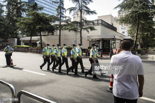 Police officers walk down the street in front of the U.S. Consulate General Chengdu in Chengdu, China, on Sunday, July 26, 2020. Theclosureof the...