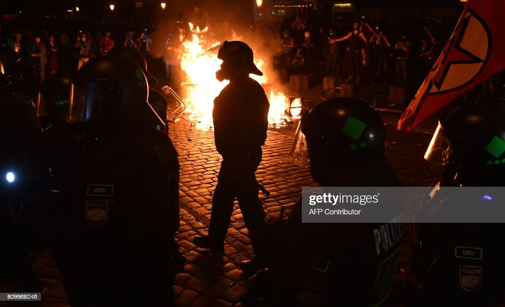 TOPSHOT - Police officers walk in front of a fire started by protesters the 'Welcome to Hell' rally against the G20 summit in Hamburg, northern Germany on July 6, 2017. Leaders of the world's top economies will gather from July 7 to 8, 2017 in Germany for likely the stormiest G20 summit in years, with disagreements ranging from wars to climate change and global trade. / AFP PHOTO / Christof STACHE