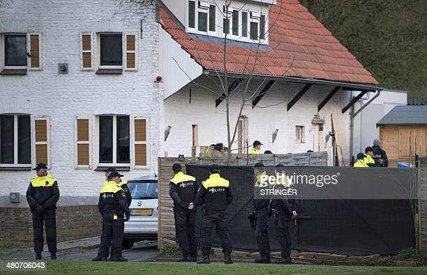 Police officers walk in front of the house used by Bandidos motorcycle club which has been closed by order of the local mayor, in Geleen, the...