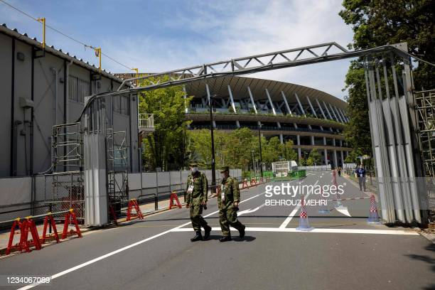 Police officers walk in front of the Olympic Stadium in Tokyo on July 20, 2021 ahead of the Tokyo 2020 Olympic Games.