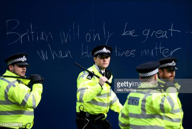 Police officers walk infront of graffiti during a Black Lives Matter protest on June 06 2020 in London United Kingdom The death of an AfricanAmerican...