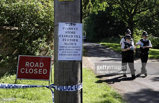 Police officers walk near a sign warning of closure due to foot and mouth disease near to a secured farm area in Normandy, Surrey, southern England,...
