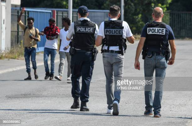 Police officers walk next to migrants in Calais on July 7 2018 Several hundred people took part in a 'solidarity' march in support of migrants in...